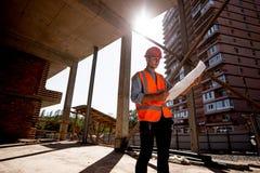Iklädd skjorta för ung man, orange arbetsväst och hjälm att undersöka konstruktionsdokumentation på byggandeplatsen inom arkivbild
