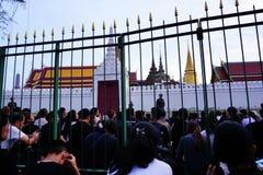 Iklädd svart för thailändskt folk, som de sitter och väntar i linje för att erbjuda beklagande för den sena konungen Bhumibol Adu arkivfoton