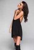 Iklädd svart klänning för sexig kvinnamodell och långa kängor i studion royaltyfria foton