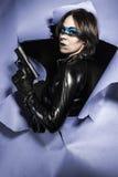Iklädd svart latex för sexig farlig kvinna som beväpnas med vapnet. Co Arkivbild