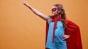 Iklädd ung flicka en superherodräkt som lyfter upp hennes näve stock video