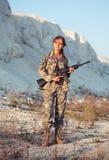 Iklädd ung kvinnlig soldat en kamouflage med ett vapen i let arkivbilder