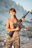Iklädd ung kvinnlig soldat en kamouflage med ett vapen i nollan royaltyfria foton