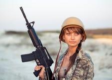 Iklädd ung kvinnlig soldat en kamouflage med ett vapen i nollan Arkivbild