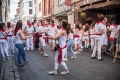Iklädd vit för folk och rött dricka och dansa i gatorna på sommarfestivalen (stora fester de Bayonne) Royaltyfria Bilder