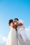 Iklädd vit för romantiska par som kysser under den blåa himlen på deras bröllopdag arkivbild