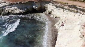 Iklädda kortslutningar för man, gymnastikskor och en T-tröja som sitter på en klippa Skummande vågor som slår den steniga kusten  lager videofilmer