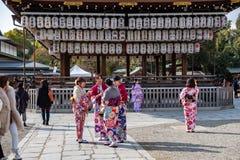 Iklädda traditionella kimonon för färgrika unga japanska flickor som pratar i tempel royaltyfria foton