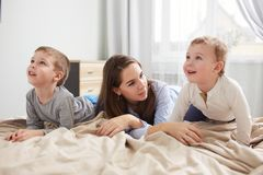 Iklätt ljust för lycklig ung moder - den blåa pajamaen lägger med hennes två lilla söner på sängen med den beigea filten i royaltyfria bilder