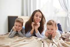 Iklätt ljust för lycklig ung moder - den blåa pajamaen lägger med hennes två lilla söner som rymmer på deras händer under deras h arkivbild