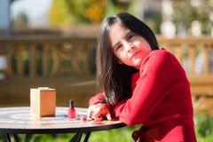 Iklätt rött sammanträde för flicka i trädgård Arkivbild