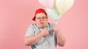 Ikl?dd barnslig stil f?r lycklig man som joyfully skrattar, medan rymma luftballonger, ultrarapid lager videofilmer
