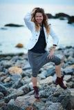 Ikl?tt vitt omslag f?r trendig flicka och bred byxa som poserar n?ra havet i aftonen fotografering för bildbyråer