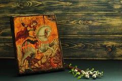 Ikone von St George die siegreiche Replik und die Weide und die Birkenzweige auf dunklem hölzernem Hintergrund Symbolisches Konze stockbilder