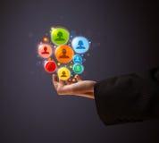 Ikonen des Sozialen Netzes in der Hand eines Geschäftsmannes Stockbild