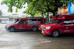 Ikonenhafter traditioneller roter LKW fährt geparkt mit einem Taxi und auf den Passagier wartend am SäulengangBusbahnhof in Chian Stockfotografie