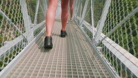 Il ¡ di Ð perde-sulla vista delle gambe femminili bianche di sport in scarpe atletiche che raggiungono attraverso il ponte sospes archivi video