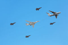 Il-76 and Tu-160 planes accompanied by fighters Stock Photos