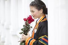 Il ager teenager in uniforme laureata con colore rosso è aumentato Immagini Stock Libere da Diritti