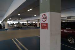 Il allower non fumatori rosso firma in tre lingue in un parcheggio sotterraneo con le automobili visibili nei precedenti fotografie stock libere da diritti