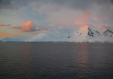 Il alpenglow sottile illumina la montagna nevosa Fotografia Stock
