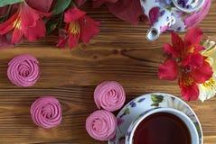 Il Alstroemeria fiorisce il piatto rosso con il vaso della tazza di tè dello zefiro Immagine Stock Libera da Diritti