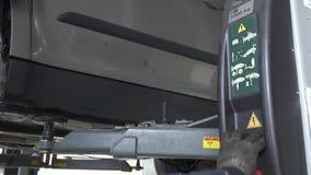 Il automaster professionale preme un bottone su un meccanismo di trasporto di sollevamento di sollevamento per abbassare l'automo stock footage