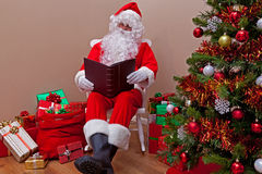 Il Babbo Natale che legge la lista fotografie stock