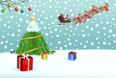 il Babbo Natale che mette regalo sulla neve vicino all'albero di Natale Fotografia Stock Libera da Diritti