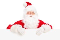 Il Babbo Natale che propone dietro un tabellone per le affissioni in bianco Immagine Stock Libera da Diritti