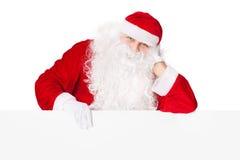 Il Babbo Natale che si appoggia sulla scheda in bianco Fotografia Stock