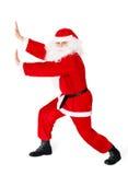 Il Babbo Natale che spinge qualcosa isolato su bianco Fotografia Stock Libera da Diritti