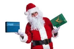 Il Babbo Natale che tiene due contenitori di regalo Immagini Stock