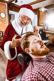 Il Babbo Natale come padrone al negozio di barbiere Fotografia Stock Libera da Diritti