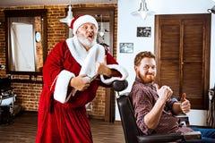 Il Babbo Natale come padrone al negozio di barbiere Fotografie Stock Libere da Diritti