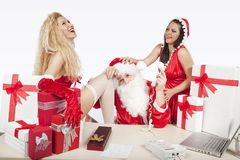Il Babbo Natale con due assistenti sexy nel suo ufficio Fotografia Stock Libera da Diritti
