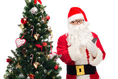 Il Babbo Natale con l'albero di Natale e dello smartphone Fotografia Stock