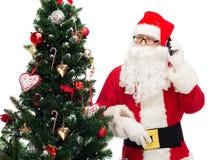 Il Babbo Natale con l'albero di Natale e dello smartphone Immagini Stock Libere da Diritti