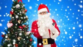 Il Babbo Natale con l'albero di Natale e dello smartphone Immagini Stock