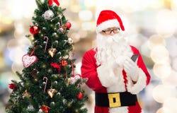 Il Babbo Natale con l'albero di Natale e dello smartphone Fotografie Stock