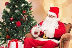 Il Babbo Natale con l'albero di Natale e dello smartphone Immagine Stock Libera da Diritti