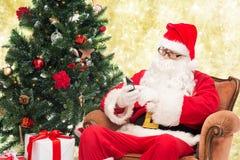 Il Babbo Natale con l'albero di Natale e dello smartphone Fotografia Stock Libera da Diritti