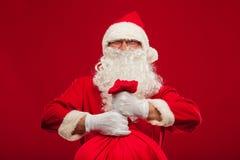 Il Babbo Natale con la grande borsa sul fondo di rosso di vetro della spalla Immagine Stock