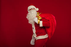 Il Babbo Natale con la grande borsa sul fondo di rosso di vetro della spalla Fotografie Stock