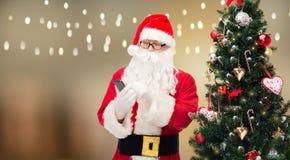Il Babbo Natale con lo smartphone all'albero di Natale Immagine Stock
