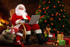 Il Babbo Natale con un computer portatile Fotografia Stock