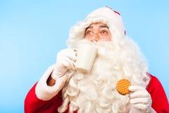 Il Babbo Natale con una tazza di caffè o un tè e un biscotto sulle sedere blu Immagini Stock