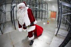 Il Babbo Natale faticoso che slaccia i regali dal sacco rosso Fotografia Stock Libera da Diritti