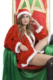 Il Babbo Natale sexy Noel che si siede in sua poltrona Immagine Stock