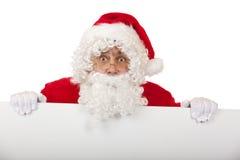 Il Babbo Natale sorpreso tiene la scheda di pubblicità Fotografia Stock